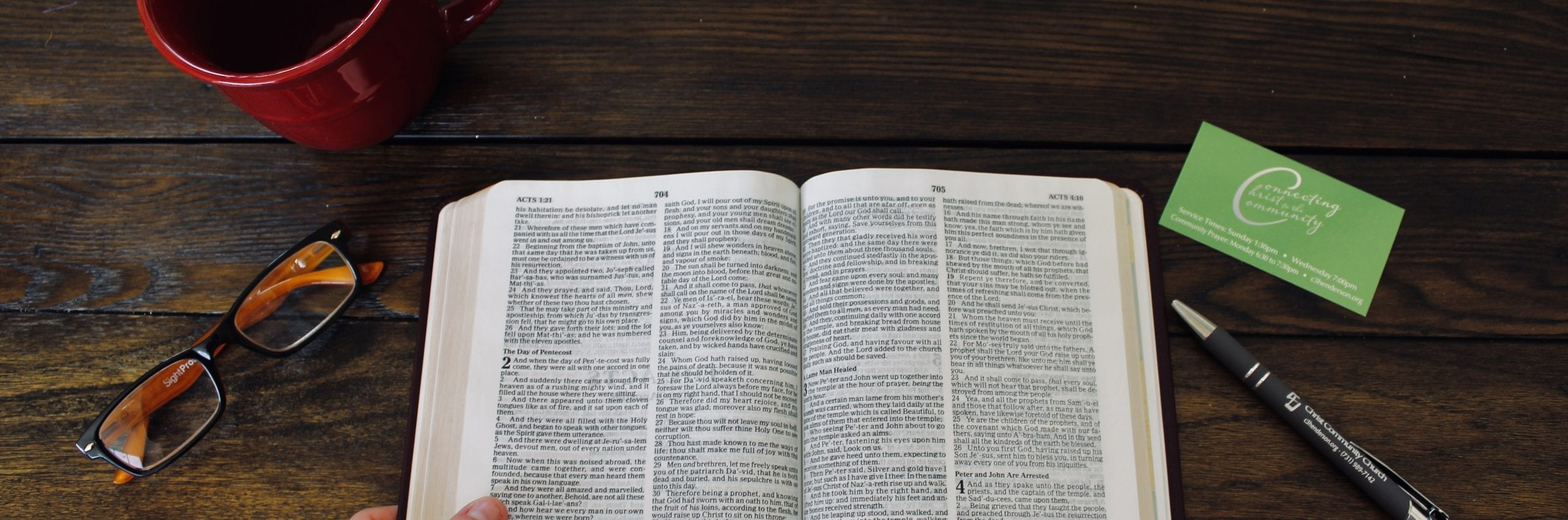 a hand on the Bible with a pen and cup of coffee - Christ Community Church The Pentecostals - Henderson, TN