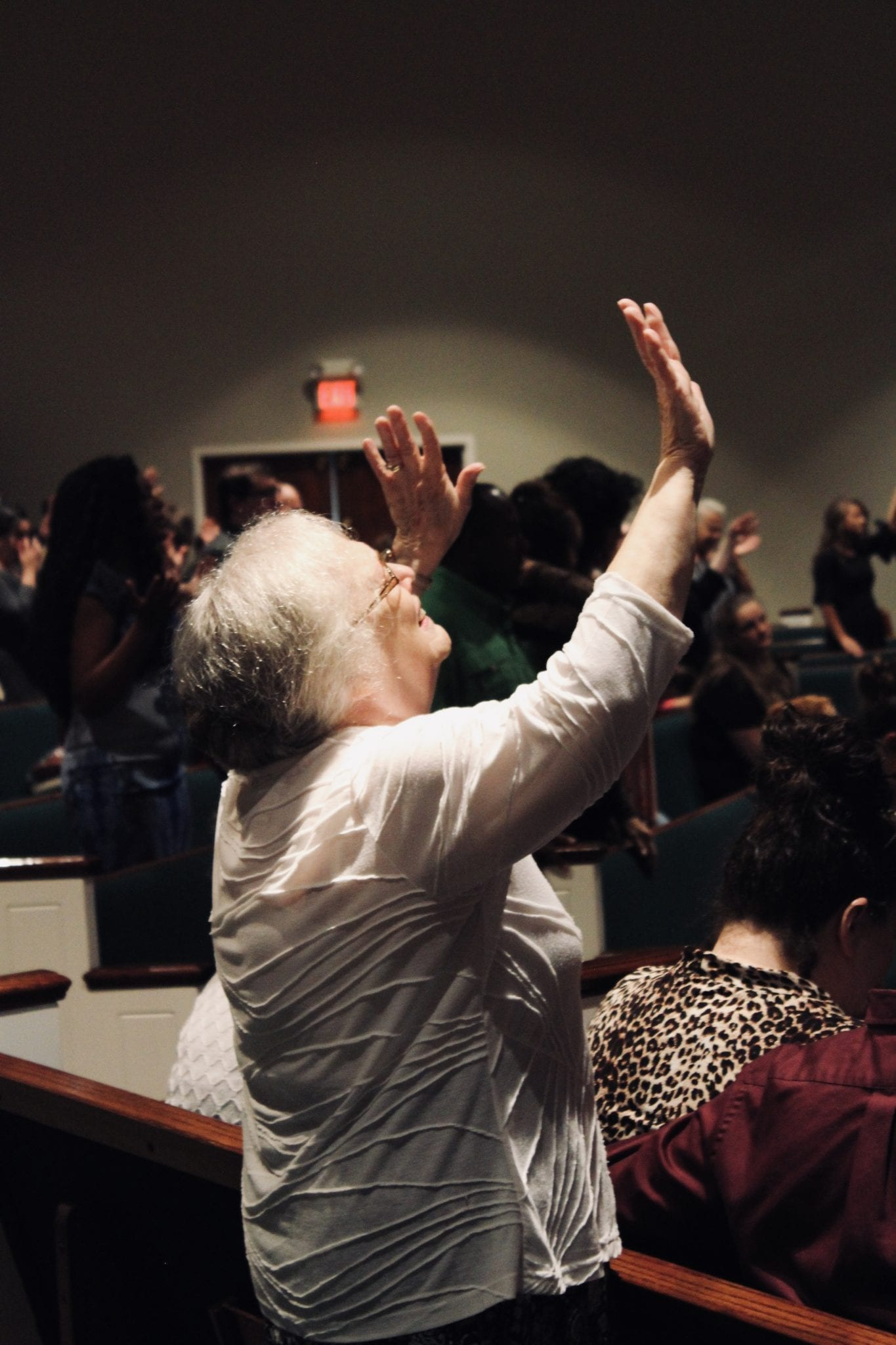 a lady worshiping in the sanctuary with others - Christ Community Church The Pentecostals - Henderson, TN